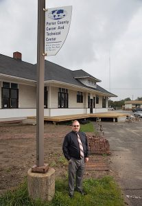 """A PASSION FOR SUCCESS"" Jon Groth, area director/principal at Porter County Career and Technical Education, stands by the historic 1912 Grand Truck rail depot that was moved onto the school campus and is being converted into a 21st century classroom."