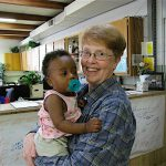 AN URGENT NEED Sister Peg Spindler holds one of her youngest clients, as another client shops.
