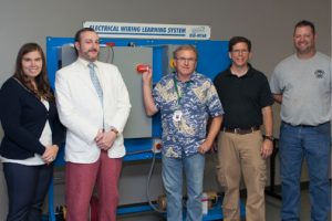 Allison Bertl, Nathan Origer, Thomas Box, Chad Huber and Andrew Pesaresi stand in front of an electrical wiring training system in the training room at Winamac Coil Spring.