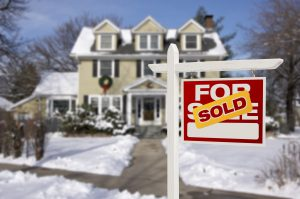 Sold Home For Sale Real Estate Sign in Front of Beautiful New House in the Snow.